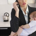 Businesswoman talking on phone holding sleeping baby